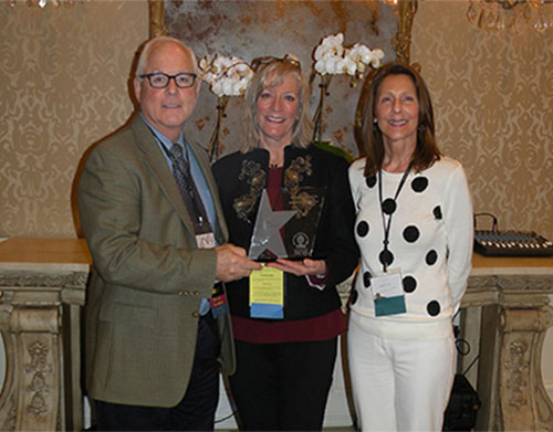 Dr. Debrah Hall, Head of The Monarch School and Institute in Houston, Texas (center) receives the National Association of Private Special Education Centers 2014 NAPSEC Award for Leadership & Innovation in Special Education. Presenting the award to Dr. Hall are Dr. Tom McCool, NAPSEC President (left) and Sherry Kolbe, NAPSEC Executive Director (right).